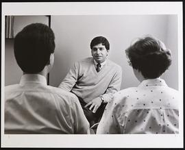 Peter Ambrose conversing with an unidentified man and woman.