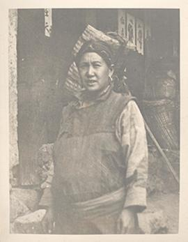 Portrait of a woman standing in a courtyard, Tibetan borderlands.