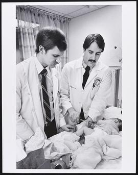 Dr. Michael Noetzel examining a patient with third year student Michael Gornet, Department of Ped...