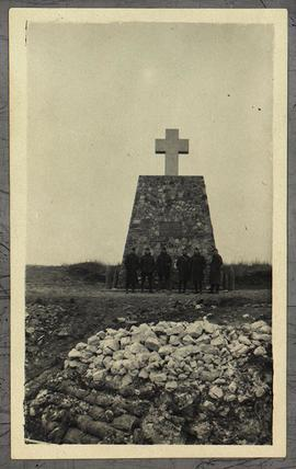 Group portrait of six unidentified soldiers standing in front of an unidentified war memorial.