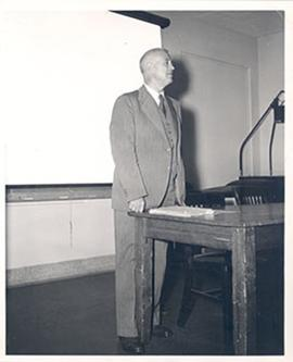 E.V. Cowdry standing at the front of a lecture hall.