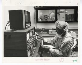 Staff member in scrubs sitting at the controls of medical equipment with an operating room in the...