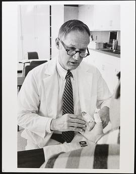 Dr. Paul Weeks examining a patient, Department of Surgery, Washington University School of Medicine.