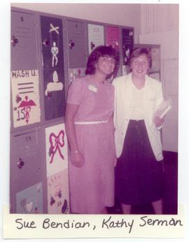 Portrait of Sue Bendian and Kathy Serman posed in front of painted lockers at a Washington Univer...