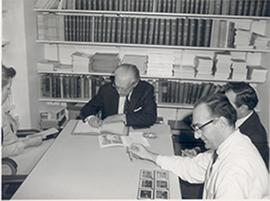 Carl F. Cori seated at a table with two other men, Roswell Park Cancer Institute, Buffalo, New York.