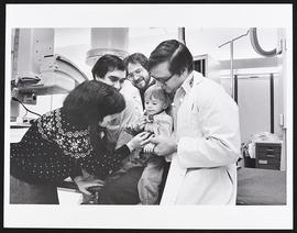 Dr. Arnold Strauss and an unidentified doctor examining a patient with third year students Rachel...