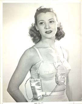 Woman modeling hearing device and battery harness attached to undergarments, for Sonotone adverti...