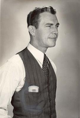 Man modeling a hearing device in a vest pocket, for Sonotone advertisement, circa 1950.
