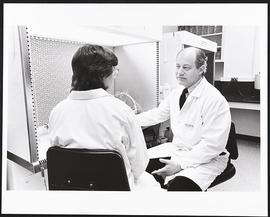 Gerald Fischbach conversing with an unidentified woman in a laboratory.
