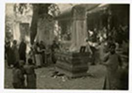 Adults and children congregating in the courtyard of a temple where memorial tablets are displaye...