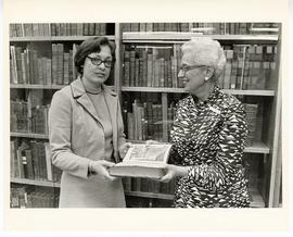 Judith Overmier and Estelle Brodman holding a book from the Max A. Goldstein rare book collection...