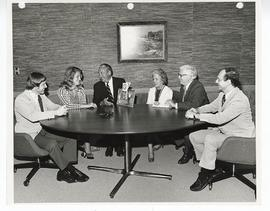 Six men and woman at a golf tournament meeting.