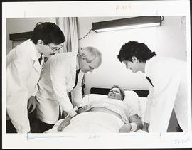 Dr. Samuel Wells examining a patient with third year students Tom Reinsel and Steven Shields, Dep...
