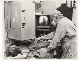 Alexis F. Hartmann, Jr. performing a procedure on a patient.