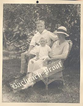Portrait proof of Alice Cowdry seated in a wicker chair with her children.