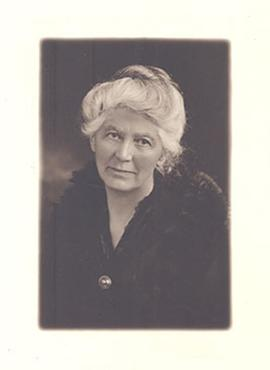 Studio portrait of Aline Cowdry wearing a black fur coat.