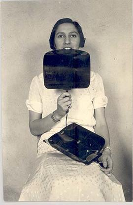 Woman demonstrating the Rhodes Audiophone while holding the Folding Dentaphone, front view, circa...
