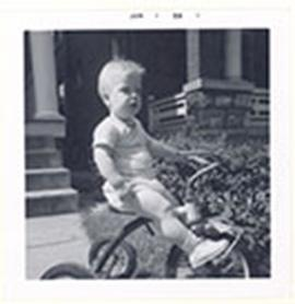 Toddler boy riding a tricycle, likely E.V. Cowdry's grandson.