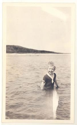 Young E.V. Cowdry, Jr. playing in the water at the beach.