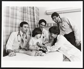 Dr. Penelope Schackelford examining a patient with three students, Department of Pediatrics, Wash...