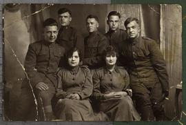Group portrait of 5 American soldiers and 2 female Red Cross volunteers.
