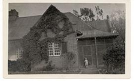 E.V. Cowdry, Jr. standing at the front door to the Cowdry home in Onderstepoort, near Pretoria, S...