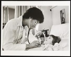 Unidentified student examining a young patient.