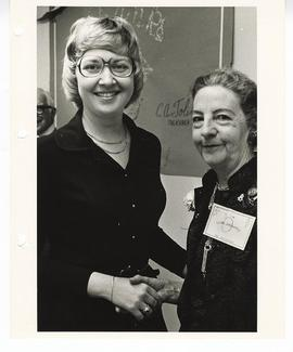 Doris England shaking hands with an unidentified woman at an appreciation party.