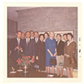 Group portrait of Alice Cowdry and ten unidentified men and women posed in a living room, Taipei,...