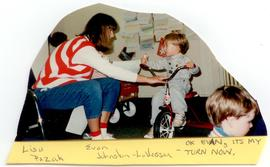 Lisa Pazak assisting Evan Johnston-LaVesser ride a tricycle, Washington University School of Medi...