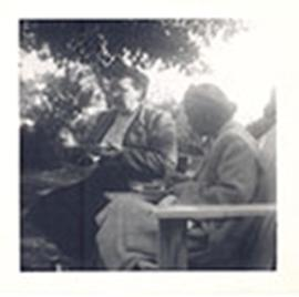 Ms. Goessling and Mildred Trotter eating in lawn chairs at the Suntzeff's garden party.