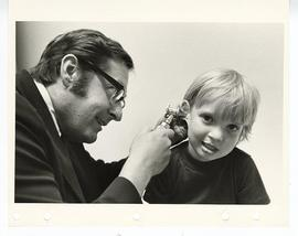 Unidentified male doctor examining a young boy's ear, St. Louis Children's Hospital.