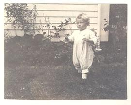 Edmund Vincent Cowdry, Jr. as a toddler, standing in a yard.