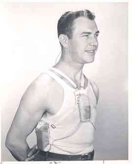 Man modeling hearing device and battery harness attached to undergarments, for Sonotone advertise...