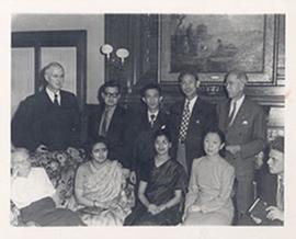 E.V. Cowdry standing in a living room with friends and colleagues, India.