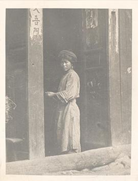 Young girl standing in a doorway, China.