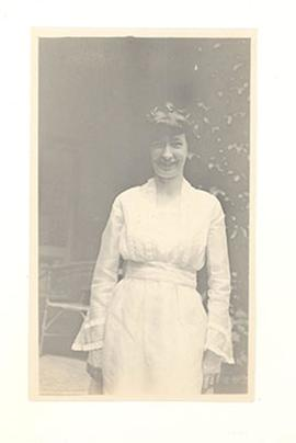 Portrait of Alice Cowdry in a white dress, standing on a patio in China.