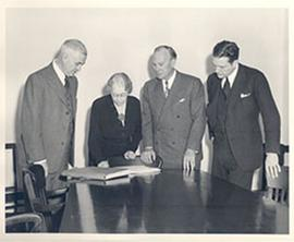 E.V. Cowdry and three unidentified people standing around a table examining a document.