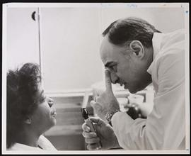 Richard D. Aach with a patient.