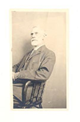Studio portrait of Nathaniel Harrington Cowdry sitting a chair and gazing off into space.