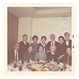 Group portrait of Alice Cowdry and ten unidentified men and women posed on one side of a dinner t...