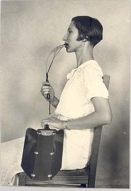 Woman demonstrating the Rhodes Audiophone while holding the Folding Dentaphone, side view, circa ...