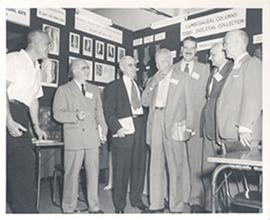 E.V. Cowdry and six other men conversing in a research display area, Second International Geronto...