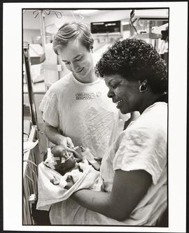 Fourth year student William Mackendrick interacting with a mother and patient, Department of Pedi...