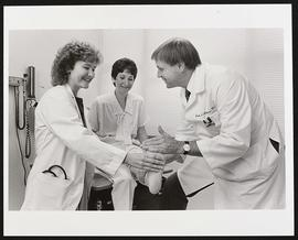 John Atkinson and an unidentified student examining a patient.
