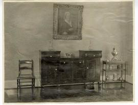 Interior view of a sideboard with a framed portrait of a woman hanging above it.
