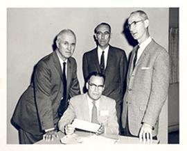 E.V. Cowdry with three unidentified men, one of whom is opening a document.