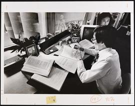 Unidentified student studying at his dormitory desk.