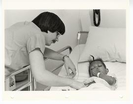 Unidentified male doctor checking on a young patient in bed, St. Louis Children's Hospital.