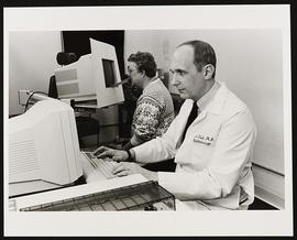 Portrait of an unidentified doctor seated at a computer.
